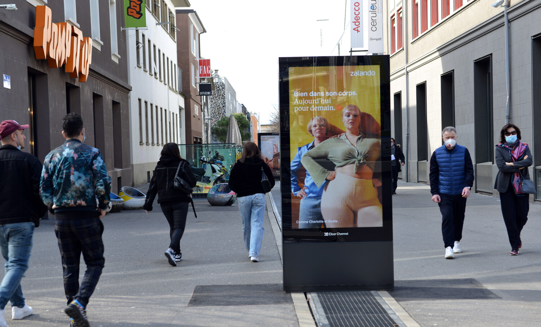 Plakat Qartier Flon in Lausanne - Digitale Werbung auf Screen im Zentrum von Lausanne – mit Plakat kaufkräftige Zielgruppe erreichen – Branding für Luxusprodukte,   hohe Reichweite, Flexibilität, dynamische Aussteuerung